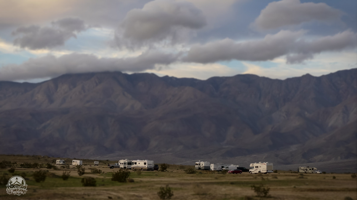 RVs in a dirt lot with mountains