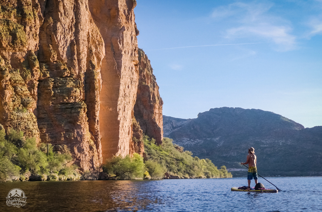 Man on paddle board next to tall cliff
