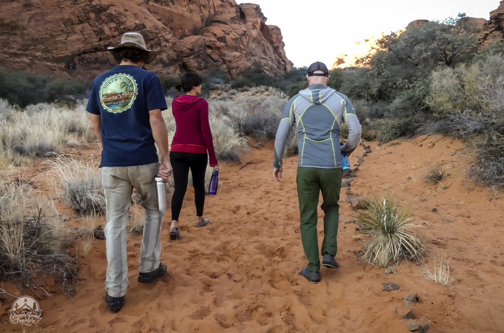 Three people on a sandy hiking trail