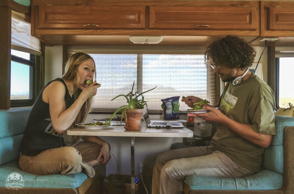 Two people eating salads in an RV